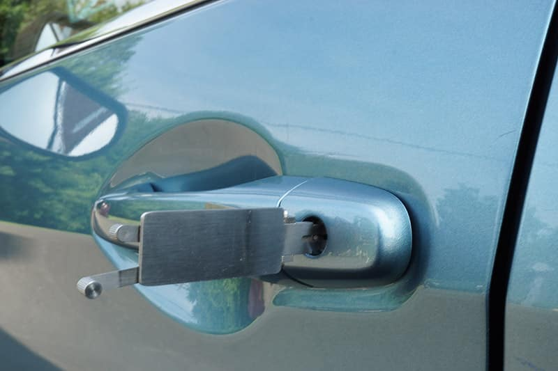 image of a car door lock being picked with professional tools