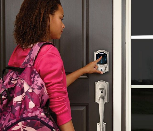 image of a young woman operation a Schlage smart lock with digital keypad